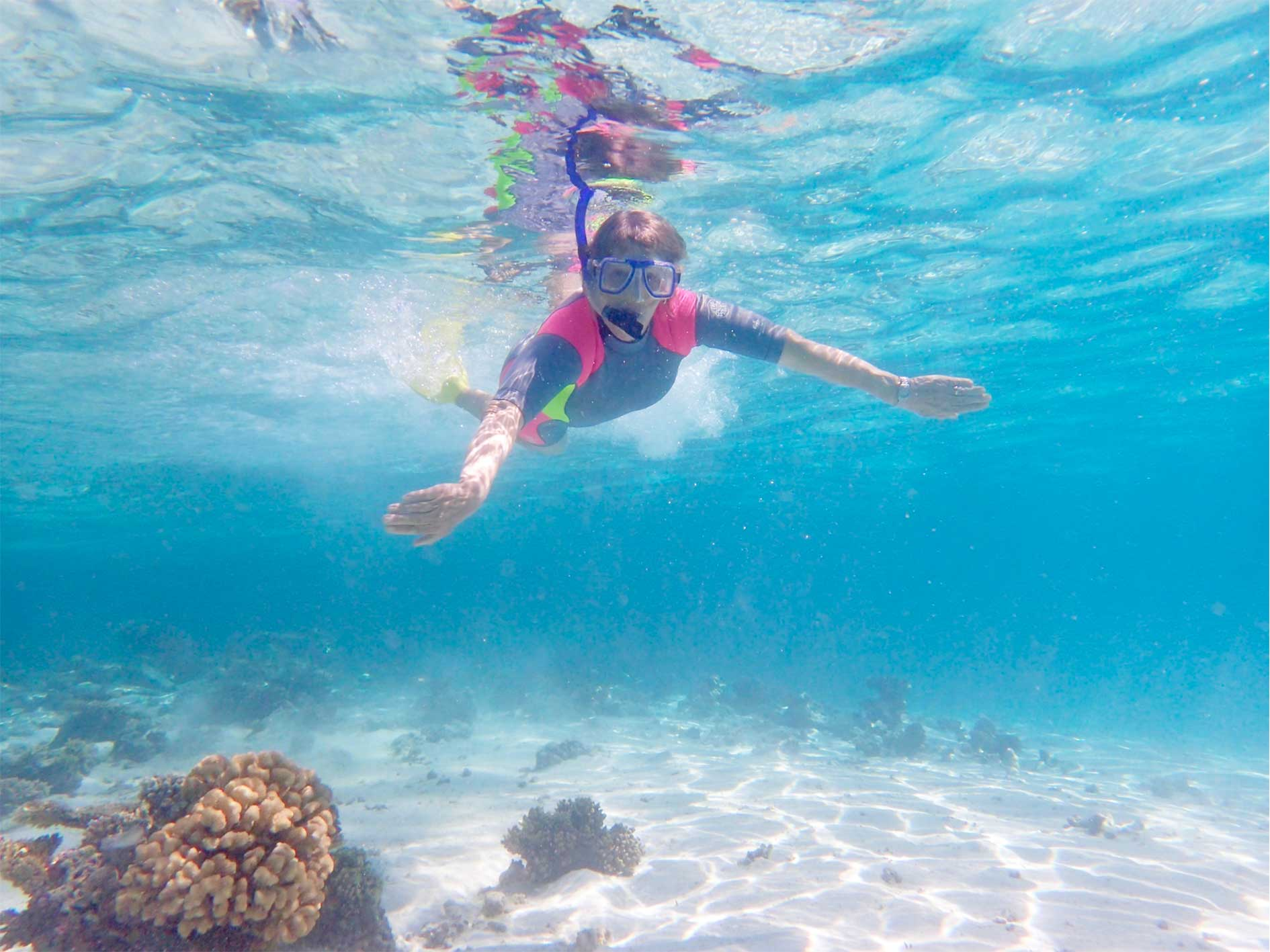 lady snorkelling through clear blue water above corals at Ningaloo Reef