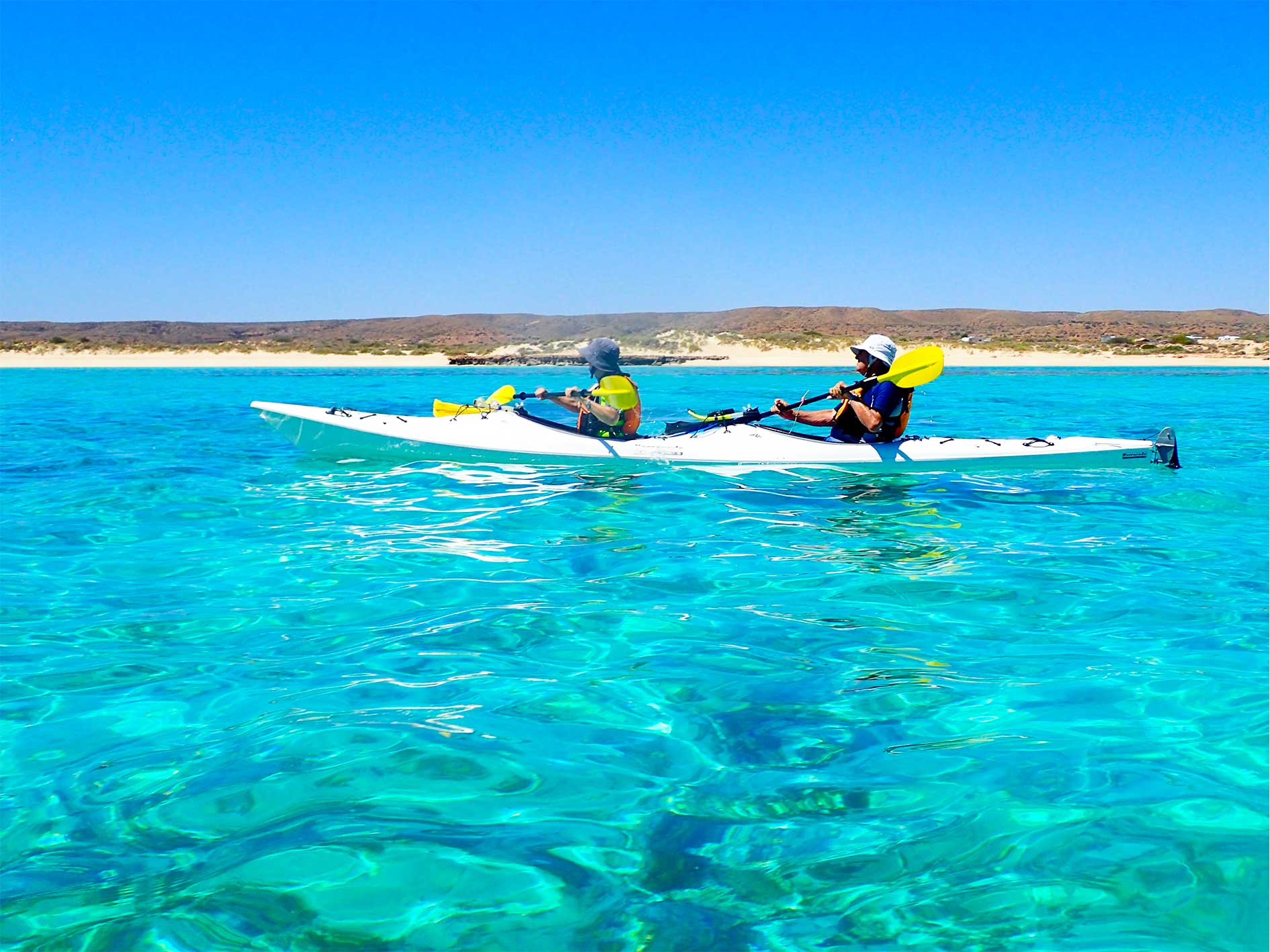 Man and woman paddling a double sea kayak on crystal clear turquoise water during a Lagoon Explorer full day sea kayak and snorkel tour at Ningaloo Reef.