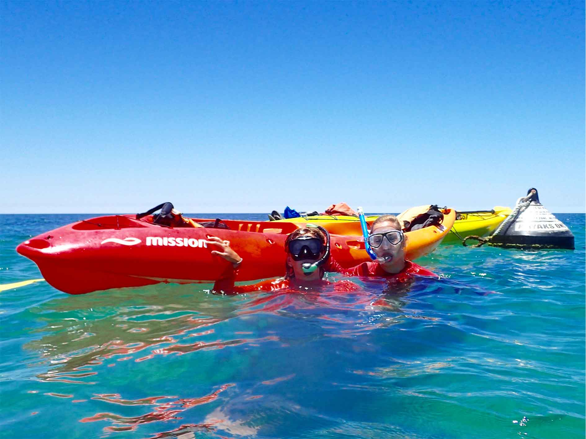 Couple wearing hire snorkel equipment in water with hire kayak at Ningaloo Reef, Exmouth, Western Australia