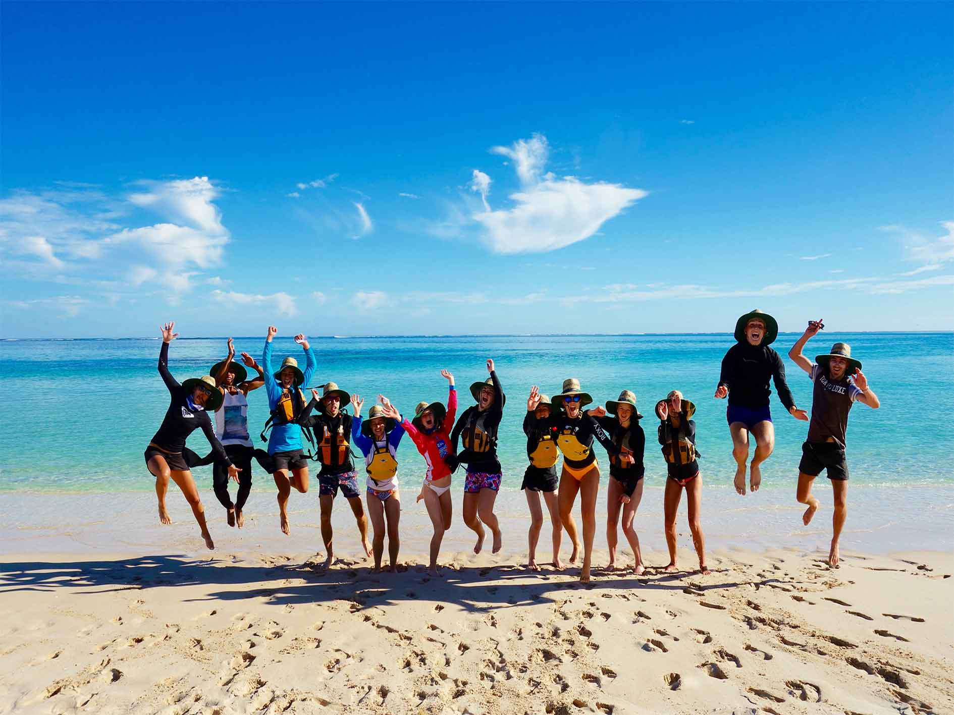 Group of people on custom tour, school group, jump on beautiful beach at Ningaloo Reef, Exmouth, Western Australia
