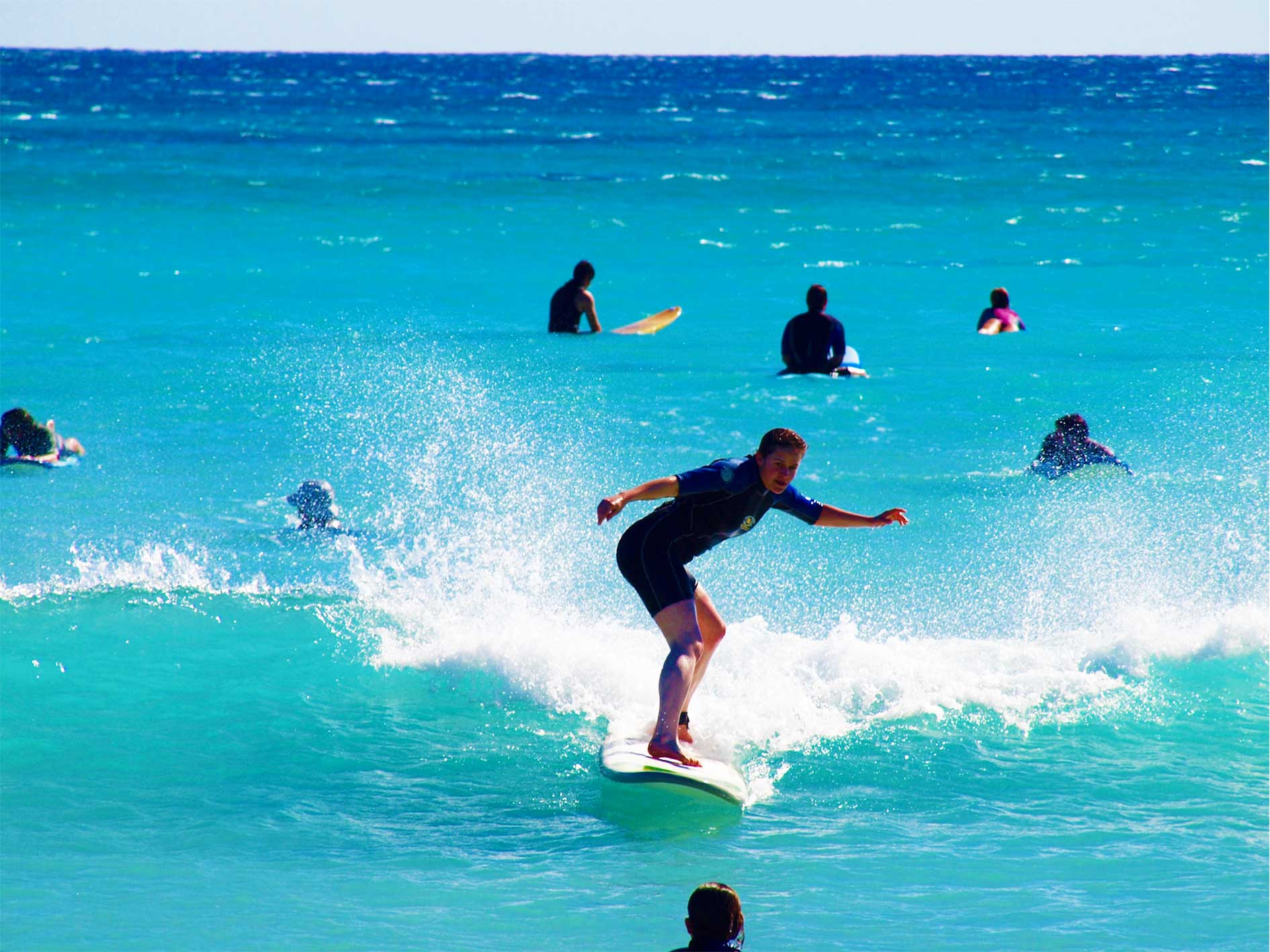 Beginner surfer rides a small wave during a learn to surf lesson in Exmouth, Ningaloo Reef, Western Australia