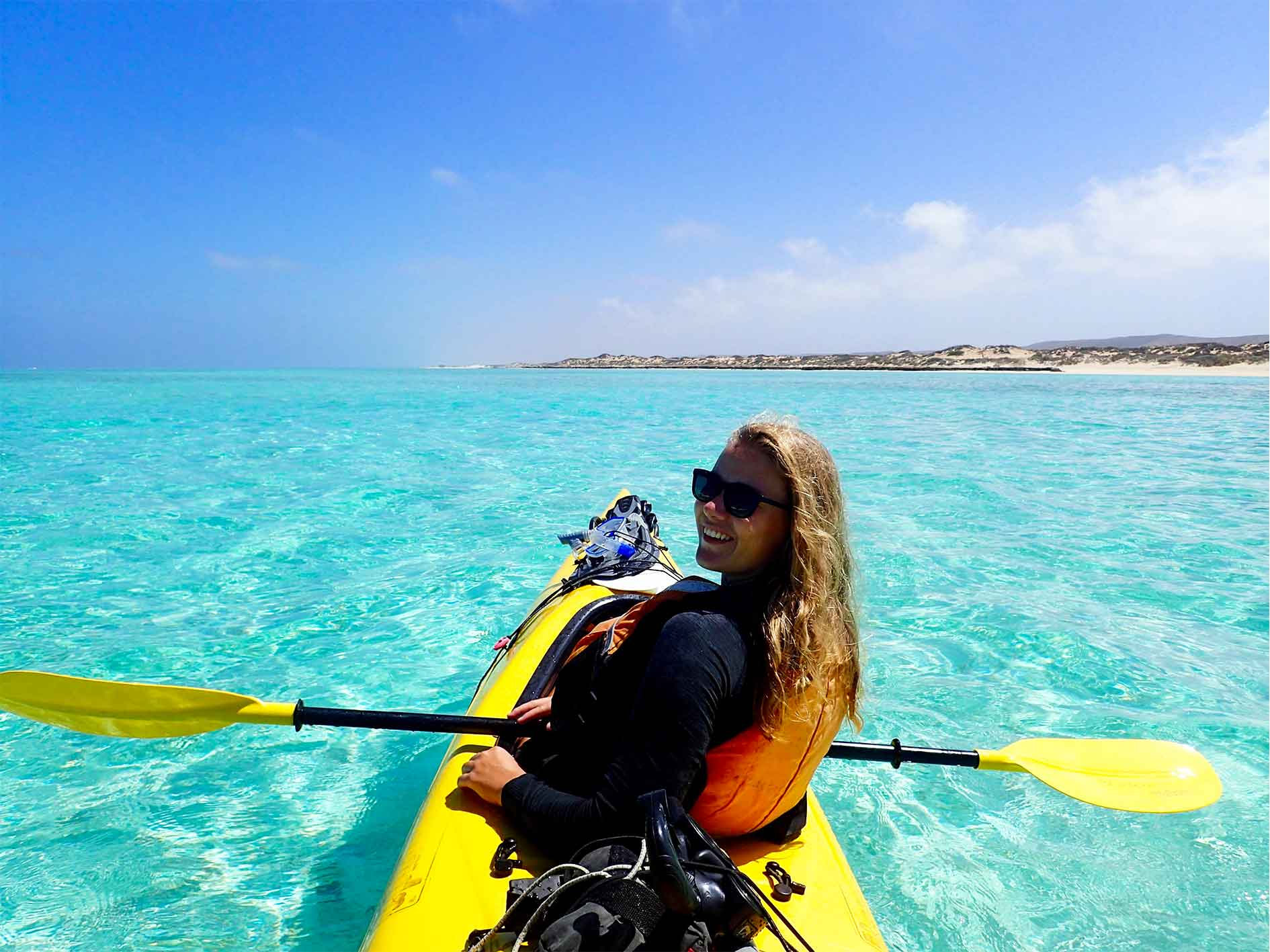 Smiling lady paddling a sea kayak on Lagoon Explorer day tour at Ningaloo Reef, Exmouth, Western Australia