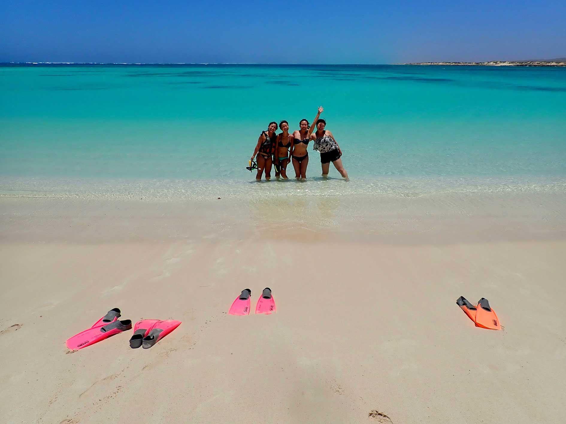 Smiling ladies stand in beautiful turquoise water at Turquoise Bay on guided snorkelling tour