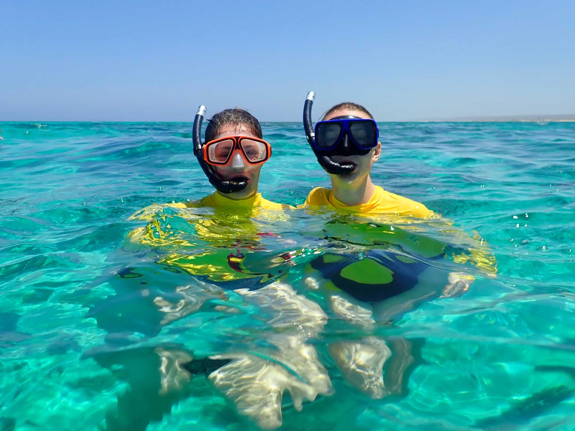 Ladies on Ningaloo Reef snorkel tour purchased by gift vouchers, smiling in clear turquoise water
