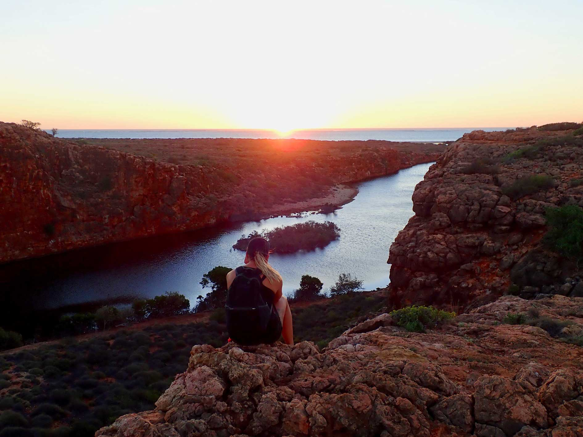 Lady at the top of Yardie Crekk Gorge enjoying a spectacular sunset on overnight kayaking, snorkelling and camping tour with Exmouth Adventure Co, Ningaloo Reef