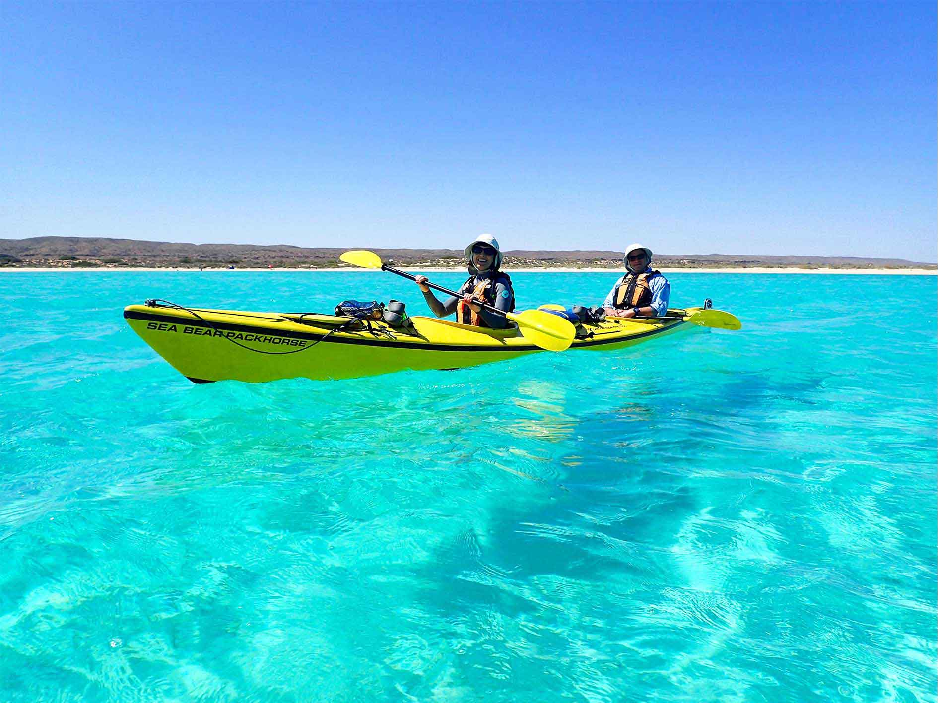 Couple paddle a double sea kayak across turquoise water on overnight sea kayaking, snorkelling, camping tour at Ningaloo Reef, Exmouth, Western Australia